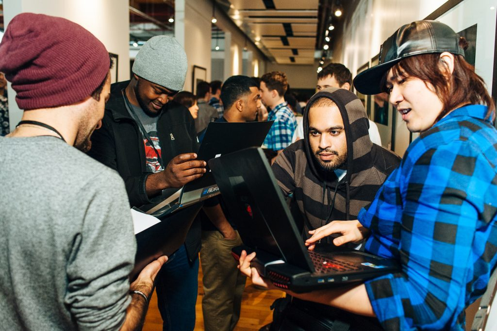 Students at the Ubisoft Toronto NXT Showcase awards party share their portfolios with each other on laptops