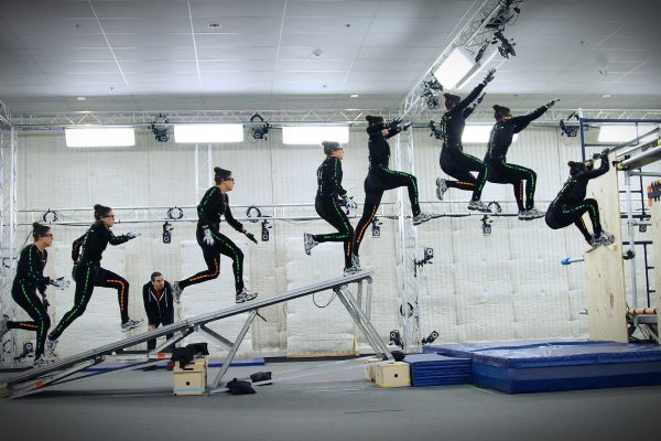 time lapse image of motion capture stunt woman run up ramp and jump on stage in the performance capture studio