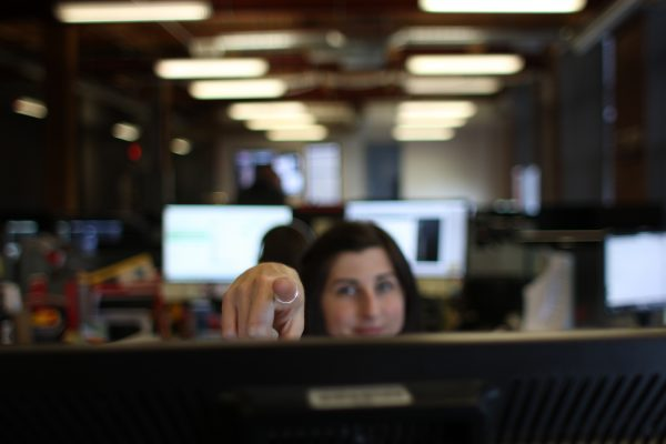 woman at desk point over computer screen directly at camera with office and screens behind her